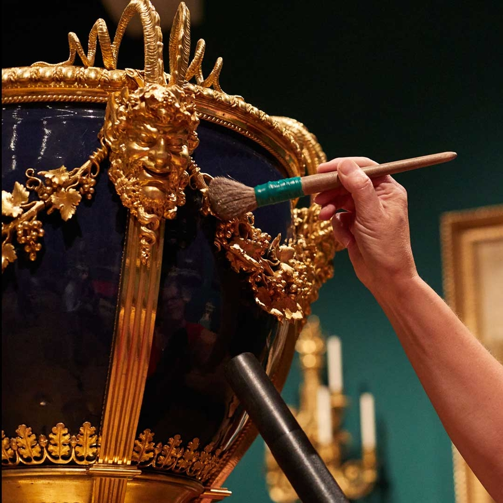 Cleaning a vase in the 'George IV: Art & Spectacle' exhibition