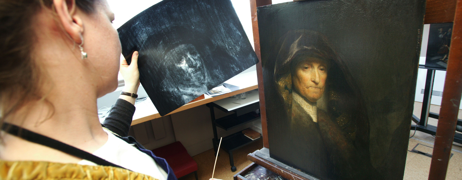 Staff restoring Rembrant picture in conservation studio